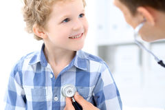 Doctor examining a child  patient by stethoscope Stock Photos
