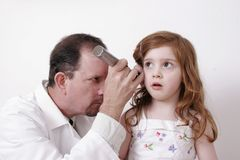 Doctor examining a child's ear. Doctor in a white coat using an otoscope to check a child' sear Stock Photos