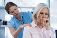 Doctor examining coughing patient stock images