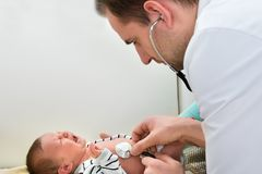 Doctor examining crying baby Stock Photo