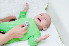 Doctor examining crying baby with stethoscope stock photos
