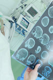 Doctor examining CT scan of patient in ICU Stock Photo