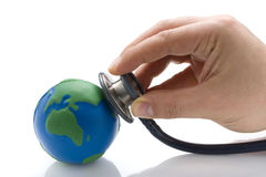 Doctor Examining Earth s Condition. Man hand with phonendoscope auscultating the planet earth represented by rubbery ball over white background Royalty Free Stock Images