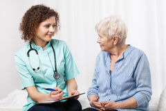 Doctor examining elderly woman Stock Images