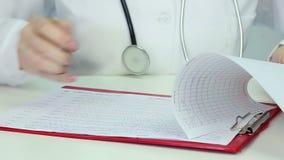 Doctor examining electroencephalogram, studying  patient's brain activity, EEG stock footage