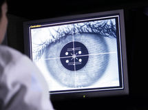 Doctor examining eye scan on computer. Doctor examining a digital eye scan on her computer screen Royalty Free Stock Photo