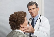 Doctor Examining Female Patient for Flu Symptoms Stock Images