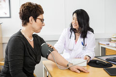 Doctor Examining Female Patient's Blood Pressure royalty free stock image