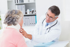 Doctor examining female patient wearing neck brace Stock Images