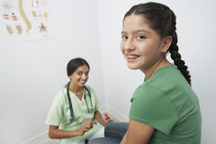 Doctor Examining Girl With Reflex Hammer. Portrait of a female doctor examining teenage girl with reflex hammer stock photography