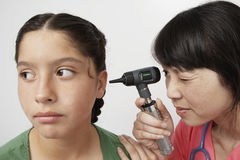 Doctor Examining Girl's Ear With Otoscope. Doctor examining little girl's ears with otoscope against white background stock images