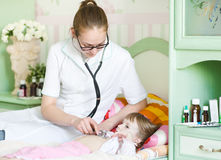 Doctor examining girl with stethoscope Stock Photography