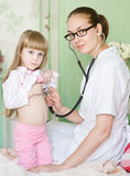 Doctor examining girl with stethoscope Royalty Free Stock Images