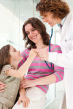 Doctor examining happy child, smiling. Royalty Free Stock Image