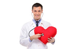 Doctor examining a heart shaped pillow Royalty Free Stock Photos