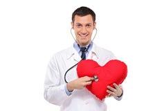 Doctor examining a heart shaped pillow Royalty Free Stock Photos