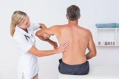 Doctor examining her patient arm