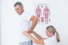 Doctor examining her patient back Royalty Free Stock Images