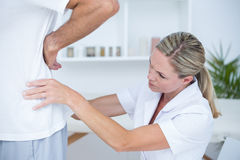 Doctor examining her patient back Stock Image
