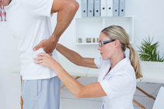 Doctor examining her patient back Royalty Free Stock Image