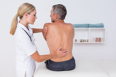 Doctor examining her patient back Royalty Free Stock Photo