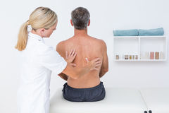 Doctor examining her patient back Stock Photography