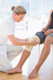 Doctor examining her patient knee Royalty Free Stock Photos