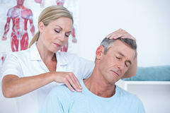 Doctor examining her patient neck Royalty Free Stock Photography