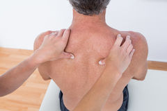 Doctor examining her patient shoulder Stock Photo