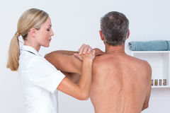 Doctor examining her patient shoulder Royalty Free Stock Photo