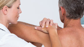 Doctor examining her patient shoulder Stock Images