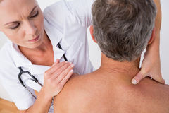 Doctor examining her patient shoulder
