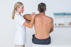 Doctor examining her patient shoulder Royalty Free Stock Images