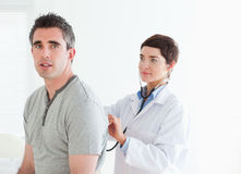 Doctor examining her patient with a stethoscope Royalty Free Stock Image