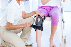 Doctor examining her patients knee Stock Images