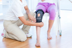 Doctor examining her patients knee. In medical office royalty free stock photography