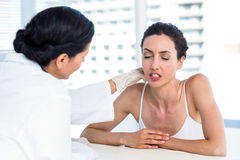 Doctor examining her patients neck Stock Photos