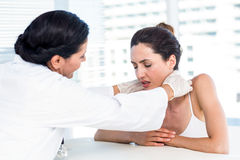 Doctor examining her patients neck Royalty Free Stock Photography
