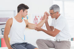 Doctor examining his patient arm Royalty Free Stock Photo