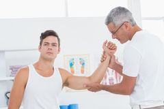 Doctor examining his patient arm Royalty Free Stock Photos