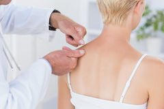Doctor examining his patient back Royalty Free Stock Photos