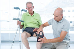 Doctor examining his patient knee Stock Photography