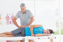 Doctor examining his patient pelvis. In medical office stock photo