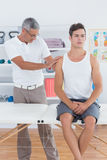 Doctor examining his patient shoulder Royalty Free Stock Image