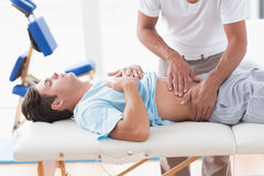 Doctor examining his patient stomach. In medical office Stock Image