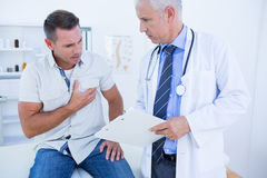 Doctor examining his patient and writing on clipboard Royalty Free Stock Images