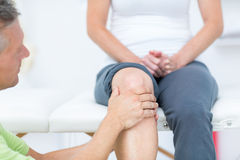 Doctor examining his patients knee Royalty Free Stock Images