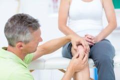 Doctor examining his patients knee Stock Image