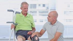 Doctor examining his patients knee