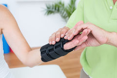 Doctor examining his patients wrist Royalty Free Stock Photography
